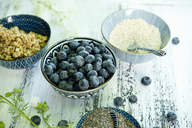 Bowls of blueberries, black chia seeds, granola and amaranth - ASF06212