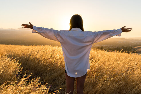Woman standing in a field of golden grass in sun drenched hills of California. - AURF01654