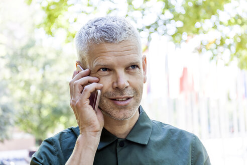 Portrait of mature man on cell phone outdoors - TCF05689