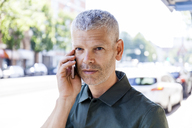 Portrait of mature man on cell phone in the city - TCF05695