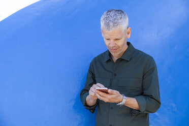 Mature man using cell phone at a blue wall - TCF05701