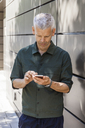 Mature man using cell phone at a wall - TCF05704