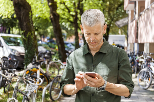 Mature man using cell phone in the city - TCF05707