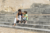 Spain, Castile and Leon, Segovia, Mother and daughter sitting on stairs - JSMF00421