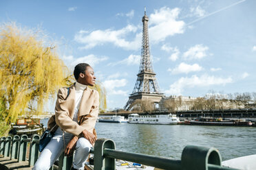France, Paris, Smiling woman at river Seine with the Eiffel Tower in the background - KIJF02000
