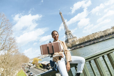 France, Paris, Woman sitting on bridge over the river Seine with the Eiffel tower in the background taking a selfie - KIJF02003