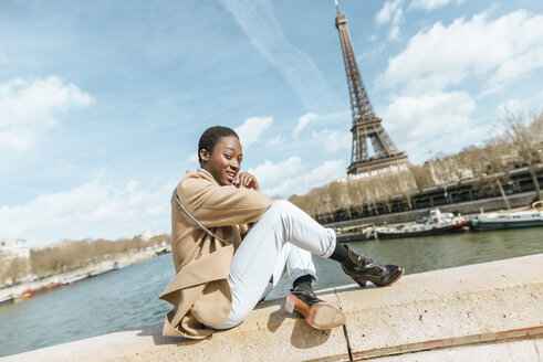 France, Paris, Woman sitting on bridge over the river Seine with the Eiffel tower in the background - KIJF02009