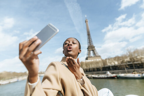France, Paris, Woman taking a selfie with the Eiffel tower in the background - KIJF02012