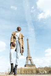 France, Paris, Woman posing with the Eiffel tower in the background - KIJF02015