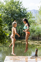 Two carefree girls jumping into pond - TCF05720