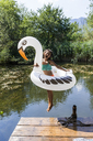 Carefree girl jumping into pond with inflatable pool toy in swan shape - TCF05723