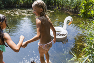 Two girls at a pond with inflatable pool toy in swan shape - TCF05726