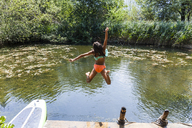 Carefree girl jumping into pond - TCF05729