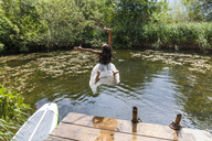 Carefree girl jumping into pond - TCF05747
