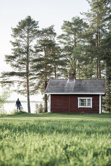 Finland, Kuopio, mother with daughter at a cottage by the lakeside in the countryside - PSIF00027