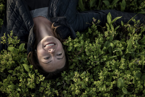 Top view of happy woman lying in a field - PSIF00036