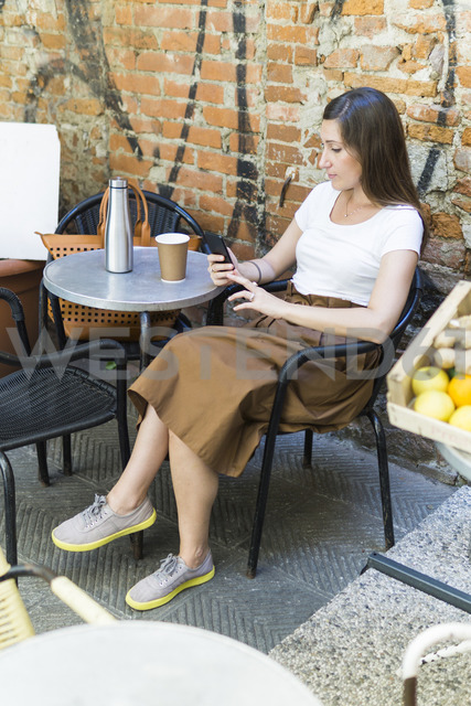 Woman using cell phone at an outdoor cafe - FBAF00001