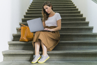 Woman sitting on a staircase using laptop - FBAF00007
