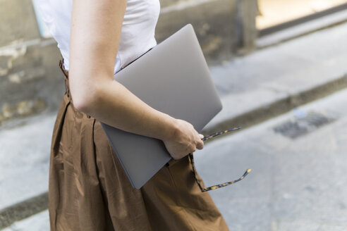 Close-up of woman carrying laptop outdoors - FBAF00010