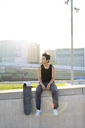Young man sitting on urban wall next to skateboard at sunset - AFVF01483