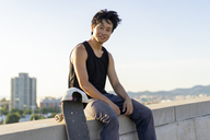Portrait of smiling young man sitting on wall next to skateboard - AFVF01486