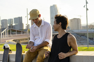 Two young men resting next to skateboards at a wall - AFVF01489