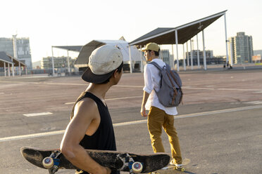 Two young men with skateboards on a parking level - AFVF01492