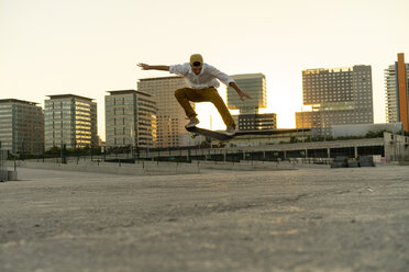 Young man doing a skateboard trick in the city at sunset - AFVF01504