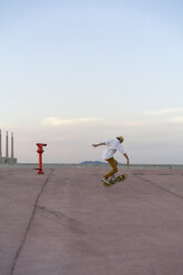 Young man doing a skateboard trick on a lane at dusk - AFVF01507