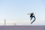 Young man doing a skateboard trick on a lane at dusk - AFVF01513
