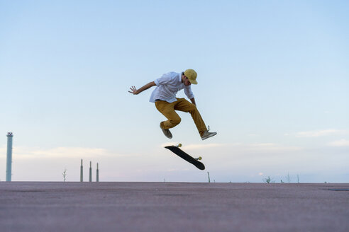 Young man doing a skateboard trick on a lane at dusk - AFVF01516
