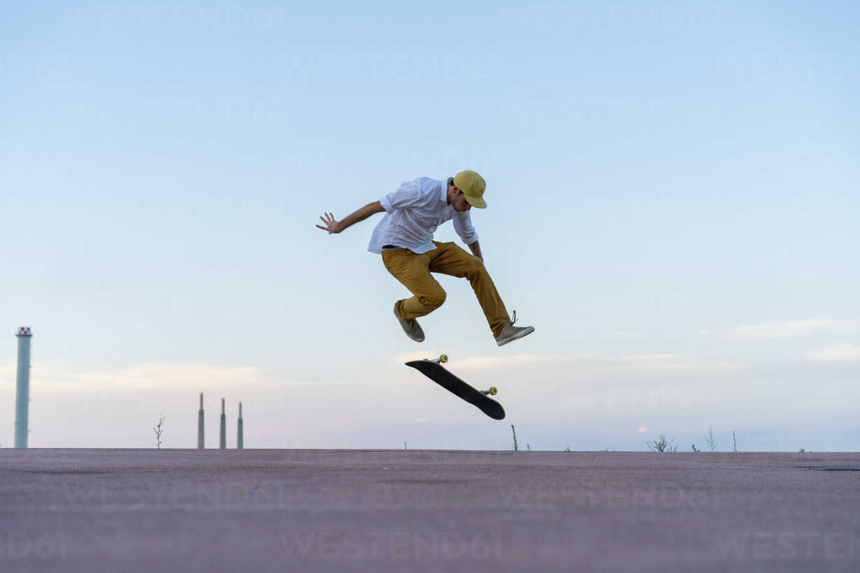 Young man doing a skateboard trick on a lane at dusk - AFVF01516 - VITTA GALLERY/Westend61