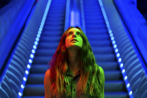 Portrait of illuminated young woman in front of blue lighted escalator looking up - AFVF01524