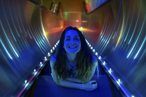 Portrait of blue illuminated young woman on steps of lighted escalator - AFVF01527