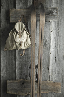 Wooden ski and old backpack on a rustic wooden wall - ASF06221