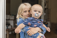 Portrait of girl holding baby boy brother at home - TCF05764