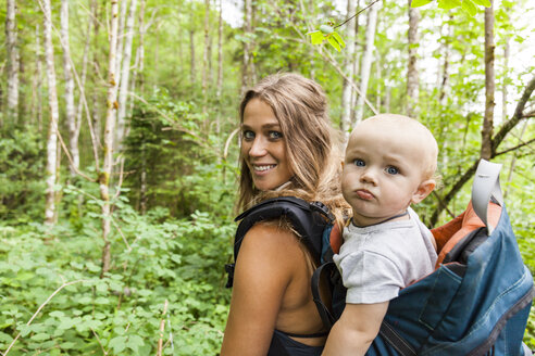 Portrait of smiling mother hiking in the woods with baby boy in backpack - TCF05767