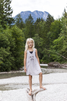 Portrait of smiling girl standing on dead wood at the riverside - TCF05773
