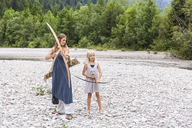 Mother and daughter with bow and arrow in the nature - TCF05788