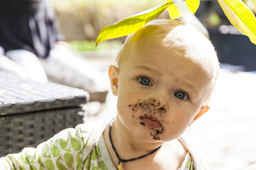 Portrait of baby boy with smeared face outdoors - TCF05803