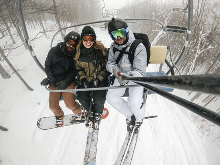 Italy, Modena, Cimone, portrait of happy friends taking a selfie in a ski lift - JPIF00003