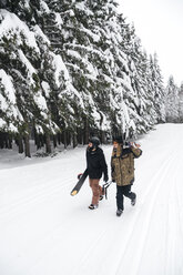 Italy, Modena, Cimone, couple with skiers and snowboard walking in winter forest - JPIF00009