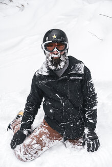 Snow-covered young man in skiwear kneeling in snow - JPIF00015