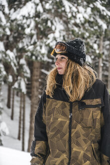 Young woman in skiwear in winter forest looking sideways - JPIF00018