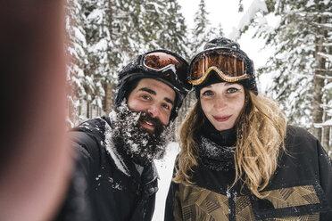 Selfie of smiling couple in skiwear in winter forest - JPIF00024