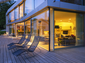 Switzerland, three deck chairs on terrace of lighted modern villa at dusk - LAF02082