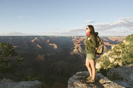USA, Arizona, Grand Canyon National Park, Young woman with backpack exploring and enjoying the landscape at sunset - GEMF02361