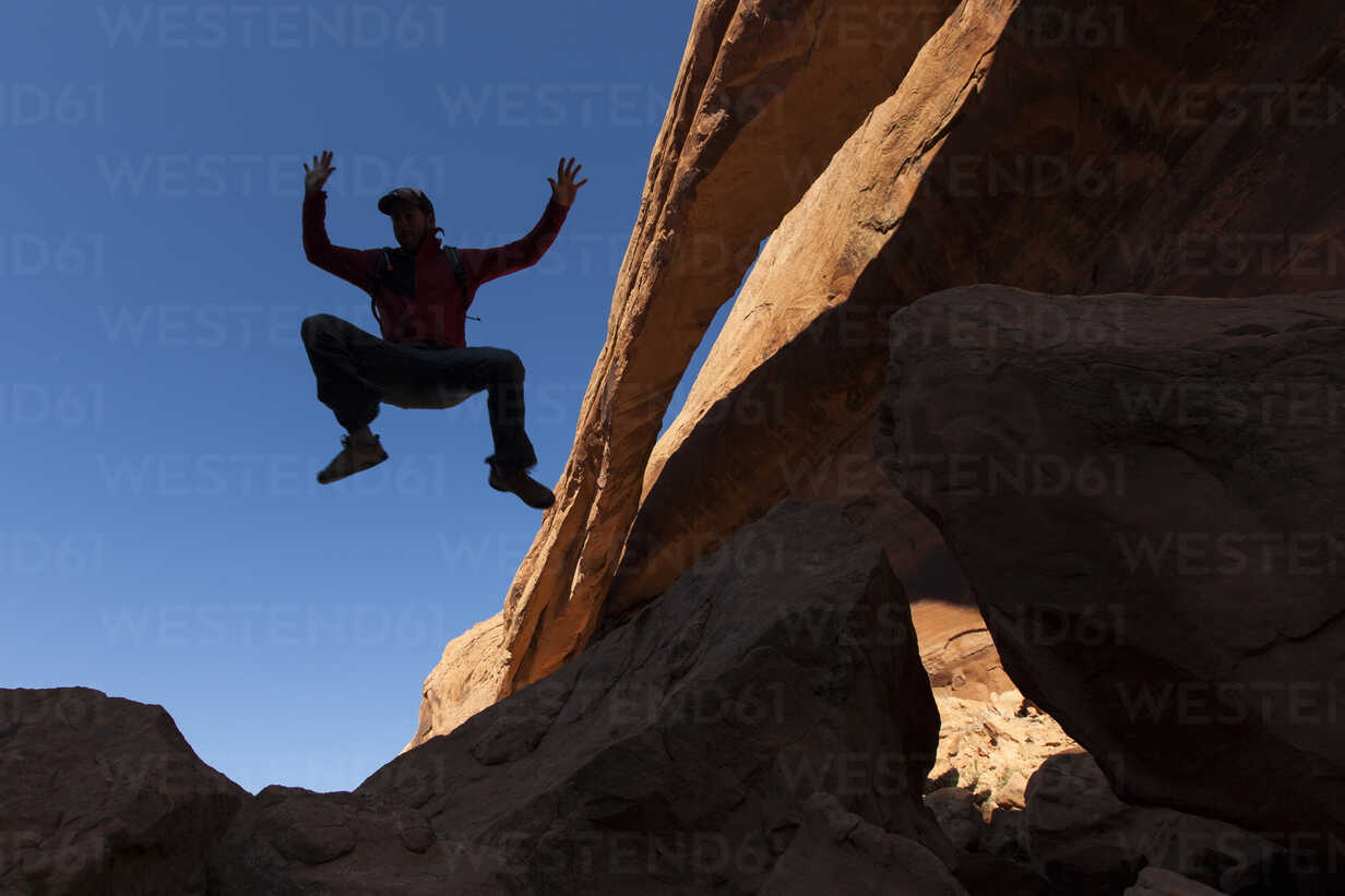 A man jumping into the air next to a natural rock arch. - AURF02013 - Cavan Images/Westend61