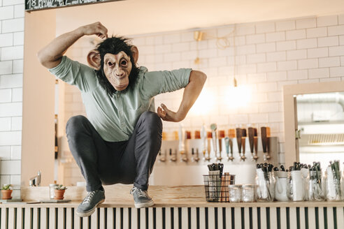 Man wearing monkey mask, sitting on counter of a bar, scratching head - GUSF01233