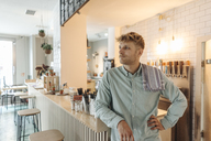 Young man working in his start-up cafe, standing at bar, daydreaming - GUSF01236